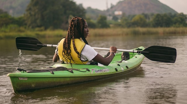 femeie de culoare in caiac verde pe lac